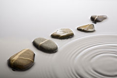 Stepping stones in rippled water. Striped pebbles forming a curve in rippled water surface Stock Photos