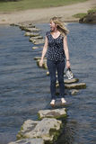 Stepping stones woman barefoot walking across cold water Royalty Free Stock Images