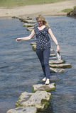 Stepping stones woman barefoot walking across river Stock Photos