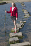 Stepping stones woman walking across river Stock Photography
