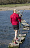Stepping stones woman walking across river Royalty Free Stock Photos