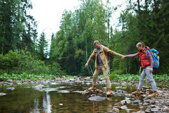 Stepping stones. Young hiker helping his girlfriend to pass over stone-path in river Stock Photo