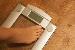 Stepping on weight scale. Royalty Free Stock Photo
