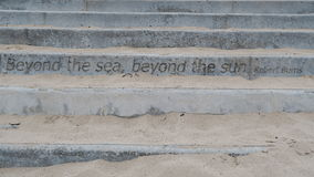 Steps on the beach with a Robert Burns quote Royalty Free Stock Images