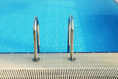 Steps in blue water pool Stock Photography