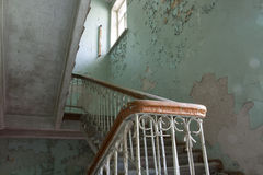 Steps in the destroyed building. Hull of an abandoned sanatorium slowly falling apart . On the stairs you can still walk, but it is not safe . In solnetsny day Royalty Free Stock Photos