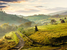 Steps down to village in foggy mountains at sunrise Royalty Free Stock Photos