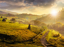 Steps down to village in foggy mountains at sunset Royalty Free Stock Images