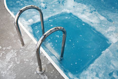 Steps in the frozen blue swimming pool Stock Photo