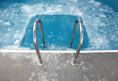 Steps in the frozen blue swimming pool Stock Images