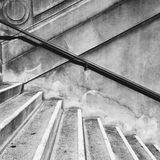 Steps and handrail. Stone steps and metal handrail on a stone wall in black and white stock photo