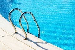 Steps with handrails in the blue pool. Pool with blue water with landscape of tropical plants and flowers on background royalty free stock photography