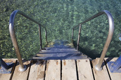 Steps with iron rails descend into clear blue water Stock Photography