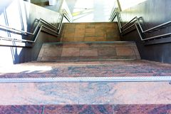 Steps leading to the basement. Marble stairs from several levels. Metal gelenders next to the stairs. stock image