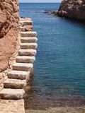 Steps next to mediteranean. Steps in the rock next to mediteranean boat slipway Royalty Free Stock Image