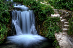 Steps next to a waterfall in green garden Stock Photo