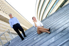 On Steps By Office Building 3. Portrait of two business colleagues outside an office building on steps.  Businessman is walking down steps; businesswoman is Royalty Free Stock Photography