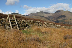 Steps over stone wall. Wooden steps over a stone wall on moorland with mountains in the background Stock Photo