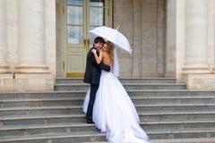 On the steps of the palace. On the steps of the royal palace newlyweds hugging under white umbrella Stock Photo