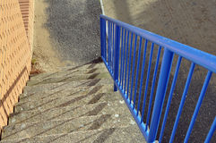 Steps with railings and shadows. A flight of steps with blue railings to right that have cast shadows Stock Photos
