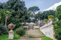 The steps and the road between the sculptures in the trees, bushes and grass in park at Villa Pamphili in Rome, capital of Italy Stock Images