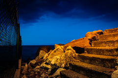Steps On Rocky Shoreline At Night Stock Images