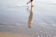 Steps on the sand. Reflection of a boy on the wet sand Stock Photography