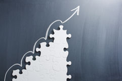 Steps shaped jigsaw puzzle and up arrow on blackboard. Stock Images