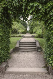 Steps thru arch to formal landscaped gardens Royalty Free Stock Image