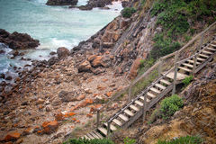 Steps to beach. Timber steps down to rocky beach Royalty Free Stock Photography