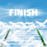 Steps to finish. A long stairway leading upward in clouds on a background blue sky with text of FINISH Stock Photo