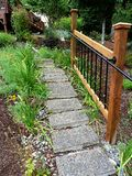 Steps to the Garden. Wood and black iron fence along concrete steps lined by daylilies and poppies in Pacific Northwest yard Royalty Free Stock Photos