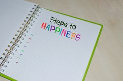 Steps to happiness written on open agenda. Over wooden background Royalty Free Stock Photography