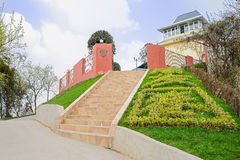 Steps to hilltop fenced building in sunny spring Stock Photos