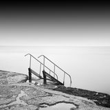 Steps to nowhere. Beautiful minimalistic black and white seascape with stairs into the sea and milk water. shot taken in daytime with long exposure. black sea Stock Photo