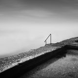 Steps to nowhere. Beautiful minimalistic black and white seascape with stairs into the sea and milk water. shot taken in daytime with long exposure. black sea Royalty Free Stock Photography