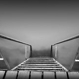 Steps to nowhere. Beautiful minimalistic black and white seascape with stairs into the sea and milk water. shot taken in daytime with long exposure. black sea Royalty Free Stock Photos