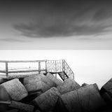 Steps to nowhere. Beautiful minimalistic black and white seascape with stairs into the sea and milk water. shot taken in daytime with long exposure. black sea Stock Images