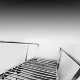 Steps to nowhere. Beautiful minimalistic black and white seascape with stairs into the sea and milk water. shot taken in daytime with long exposure. black sea Royalty Free Stock Image