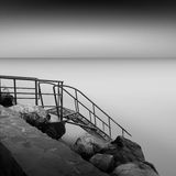 Steps to nowhere. Beautiful minimalistic black and white seascape with stairs into the sea and milk water. shot taken in daytime with long exposure. black sea Stock Photography