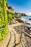 Steps to the rocky shore from the old town. Ancient european city Sozopol on a rocky shore near sea in summer. piere and steps to sea shore Royalty Free Stock Image