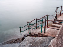 Steps to the sea, rusty, old and worn. Royalty Free Stock Photo