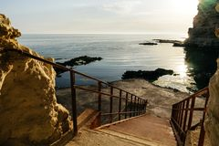 Steps to the sea stone beach. The setting sun is reflected in the water stock photography