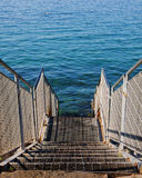 Steps to the transparent Adriatic sea waters on the free strand Stock Image