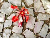 Sterbende Lilienblume auf der schmutzigen cobbled Pflasterung stockbild