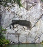 Sterbender Löwemonument Deutscher: Lowendenkmal schnitzte auf dem Gesicht der Steinklippe mit dem Teichvordergrund in Luzern, die Stockbild