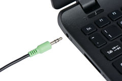 Stereo audio terminal of laptop. Closeup of stereo audio cable and terminal at a laptop computer, isolated on white stock image
