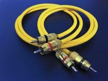 Stereo audiouitbreidings gele kabel die op blauwe achtergrond wordt geïsoleerd stock afbeeldingen