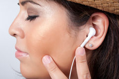 Stereo Earbud Headphones. An attractive Hispanic woman listening to and getting into the music playing through her stereo earbud headphones Royalty Free Stock Photos