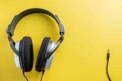 Stereo- hörlurar på gul bakgrund Kopiera utrymme för text Royaltyfri Fotografi
